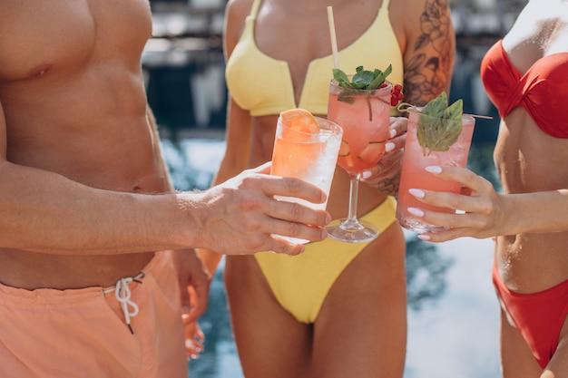 Homme avec deux femmes au bord de la piscine buvant des cocktails et s'amusant au bord de la piscine