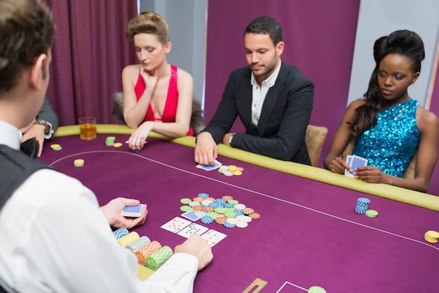 Homme et deux femmes jouant au poker