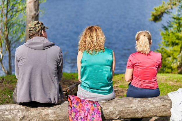 Un homme et deux femmes sont assis au bord d'un lac forestier