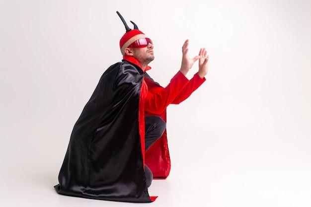 Homme diabolique étrange à lunettes de soleil et costume d'halloween rouge noir posant