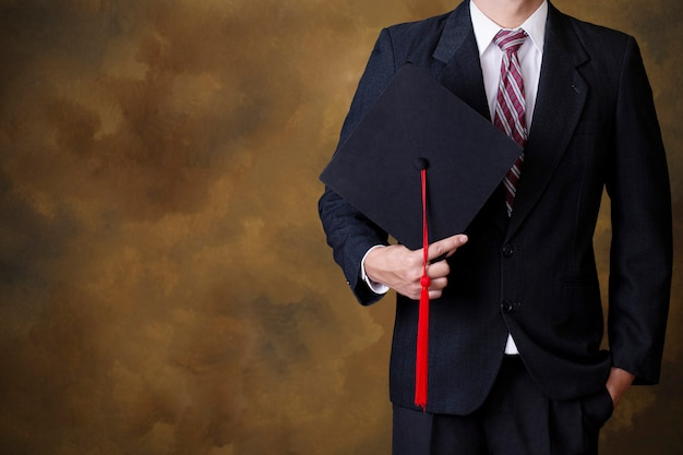 Homme diplômé tenant une casquette de graduation noire. fond