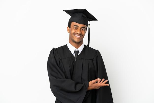 Homme diplômé d'université afro-américaine sur fond blanc isolé présentant une idée tout en regardant en souriant vers