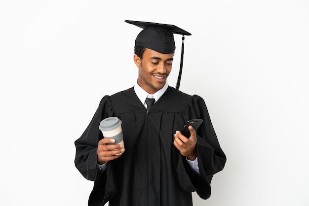 Homme diplômé de l'université afro-américaine sur fond blanc isolé tenant du café à emporter et un mobile