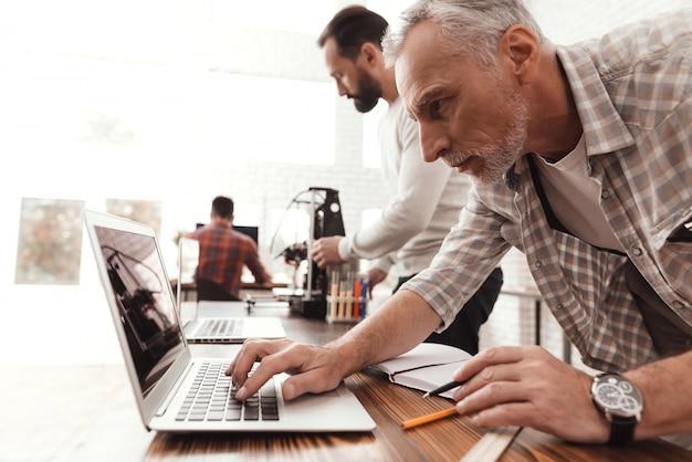 L'homme dirige le processus de démarrage et d'impression d'une imprimante.