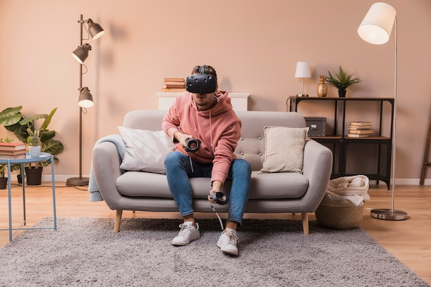 Homme, divan, jouer, virtuel, casque à écouteurs
