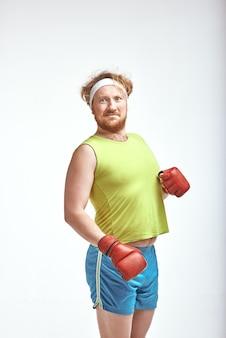 Homme dodu barbu aux cheveux rouges portant des vêtements de sport et des gants de boxe rouges