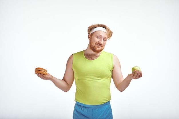 L'homme dodu barbu aux cheveux rouges tient une pomme et un sandwich