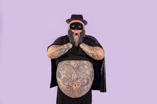 Un homme dodu choqué en costume de héros tient les joues debout sur fond violet