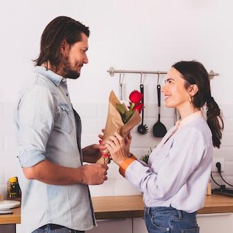 Homme donnant un bouquet de roses rouges à une femme dans la cuisine