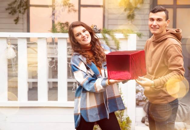 Homme donnant un cadeau de noël à sa petite amie ils tiennent une boîte rouge avec un cadeau de la saint-valentin