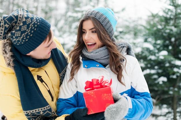 Homme donnant un cadeau rouge sa petite amie en hiver