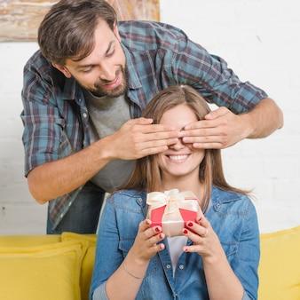 Homme donnant un cadeau de la saint-valentin à une petite amie qui couvre ses yeux