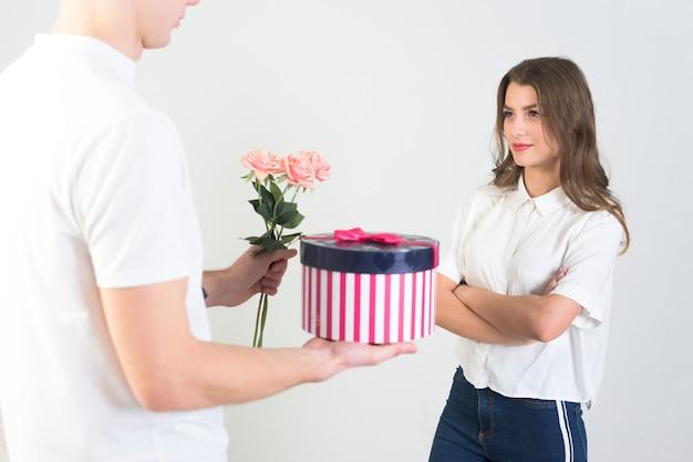 Homme donnant des cadeaux à une femme insatisfaite
