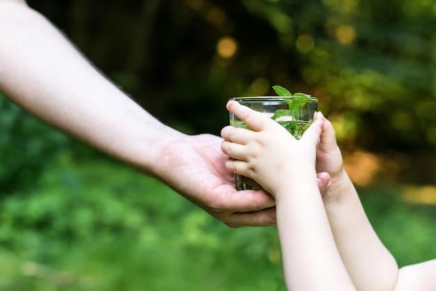 Homme donnant de l'eau à un enfant