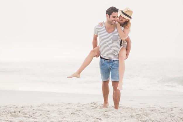 Homme donnant un piggy à la femme sur la plage
