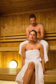 Homme donnant à sa petite amie un massage du cou dans un sauna