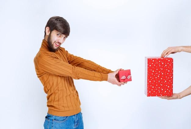 Homme donnant sa petite boîte cadeau rouge et en prenant une grosse.