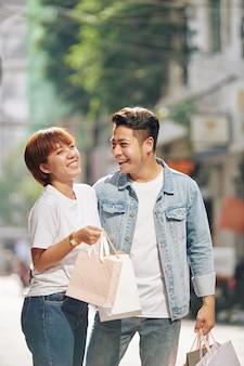 Homme donnant des sacs en papier à petite amie
