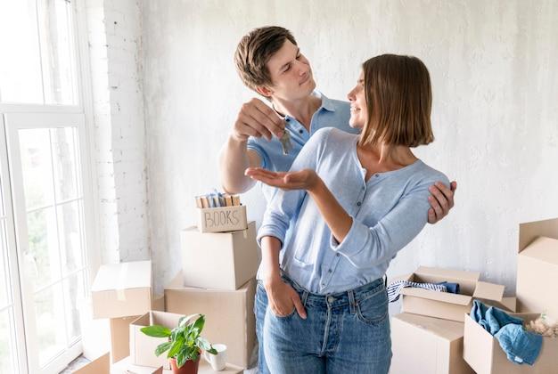 Homme donnant à son partenaire les clés de leur nouvelle maison