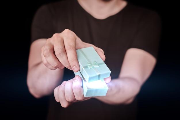 L'homme donne un cadeau dans une boîte cadeau. cadeau d'ouverture de la saint-valentin. petit coffret cadeau d'anniversaire de l'homme. petite notion surprise. fond noir.
