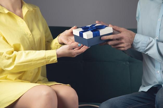 Un homme donne un cadeau à une femme assise sur un canapé. le concept de vacances en famille