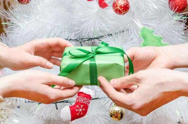 Un homme donne un cadeau à une femme contre le sapin de noël blanc. moment joyeux