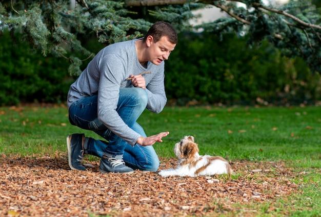 L'homme donne des commandes à un chien, la formation d'un chiot à l'extérieur