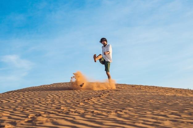 Un homme donne des coups de pied dans le sable dans un désert rouge. éclaboussure de concept de colère.