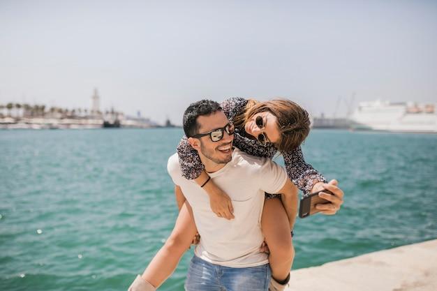 Homme, donner, elle, petite amie, promenade, sur, prendre, autoportrait, sur, téléphone portable, près, de, mer