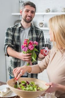 Homme, donner, présent, fleurs, à, femme, à, bol, dans, cuisine