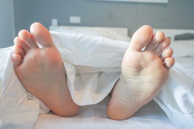 Homme dormant dans la chambre se concentrer sur les pieds