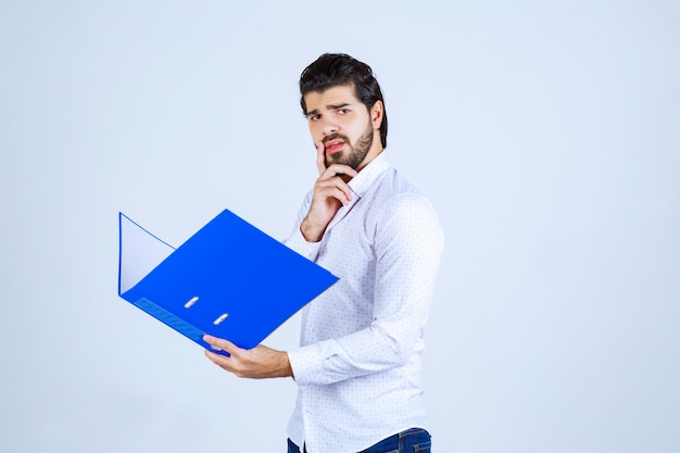 L'homme avec un dossier bleu a l'air épuisé et insatisfait