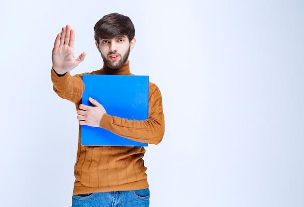 Homme avec un dossier bleu arrêtant quelque chose.