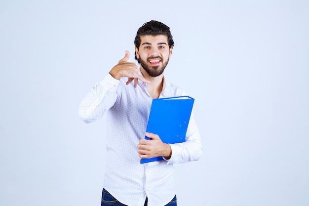 Homme avec un dossier bleu demandant d'appeler