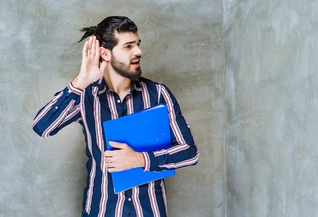 Homme avec un dossier bleu écoutant une information privée.