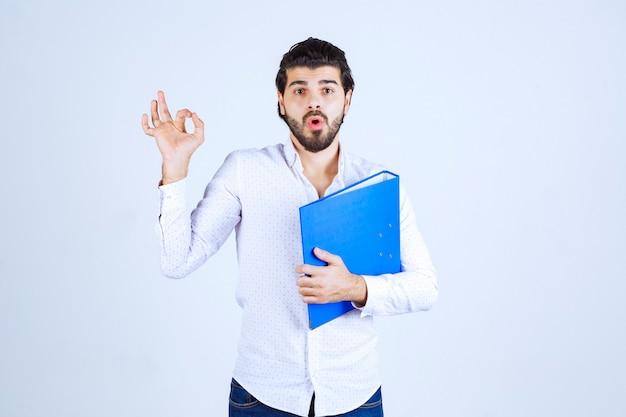 Homme avec un dossier bleu montrant un signe de plaisir