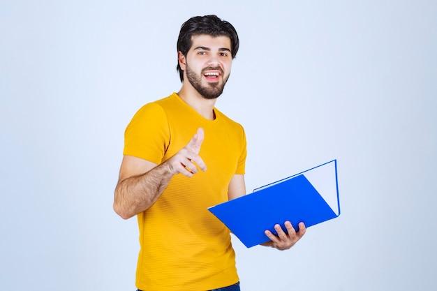 Homme avec dossier bleu pointant son collègue et souriant.