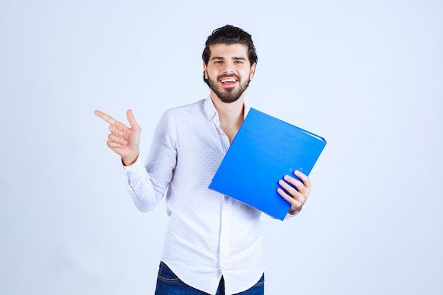 Homme avec un dossier bleu présentant son collègue à gauche