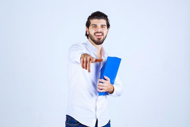 Homme avec dossier bleu remarquant son collègue