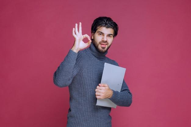 Homme avec dossier gris fait signe de la main de jouissance.