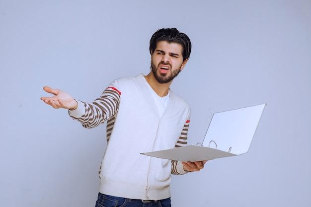 Homme avec un dossier de rapport et pointant quelqu'un sur la gauche.