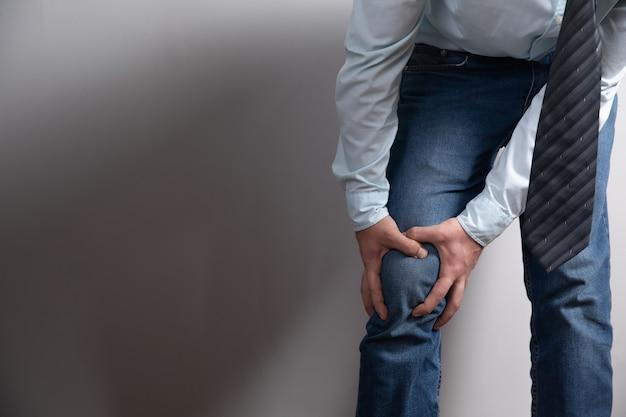 Un homme a une douleur au genou sur une surface grise