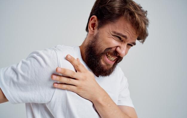 L'homme a une douleur à l'épaule et une luxation de t-shirt blanc