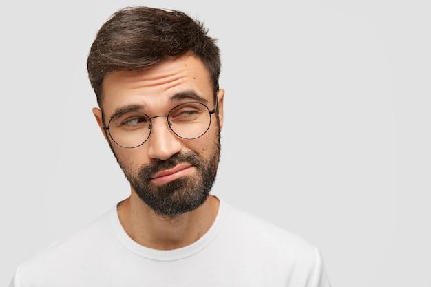 Homme douteux désemparé avec une barbe épaisse et sombre, regarde avec hésitation de côté, lève les sourcils avec étonnement