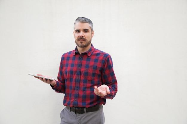 Homme douteux avec tablet pc et à la recherche