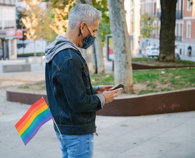 Homme avec drapeau arc-en-ciel à l'aide de smartphone en ville