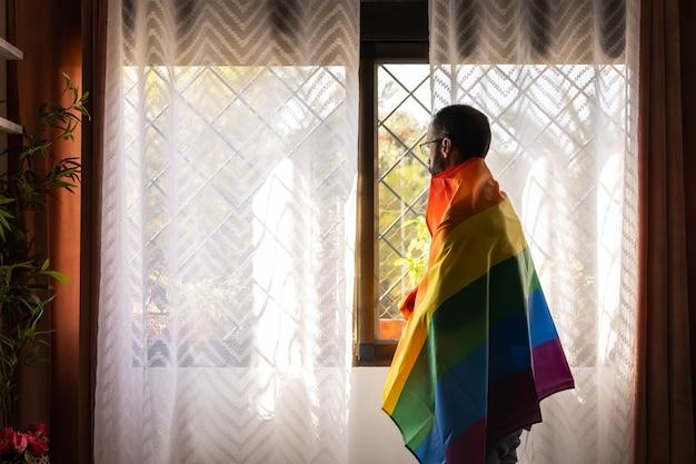 Homme avec drapeau lgbt sur les épaules en regardant par la fenêtre à l'extérieur