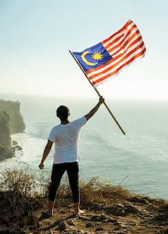 Homme avec le drapeau malaisien de la malaisie au sommet de la montagne