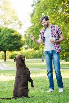 Homme dressant son chien dans un parc