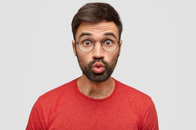 Un homme drôle attrayant avec une expression surprise garde les lèvres arrondies, envoie un baiser,